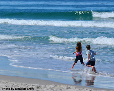 Photo of children playing in surf by